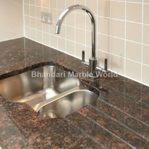 Modern 1.5 bowl kitchen sink, with chrome mixer tap, recessed into granite work surface.